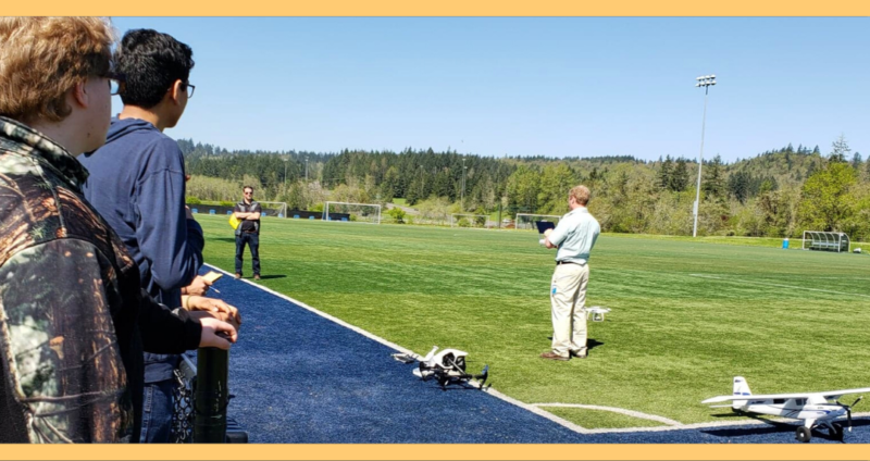 Image from the Drone Session at Hands on Career Day. Session was held on a sports field, and students lined up to view drone flights.