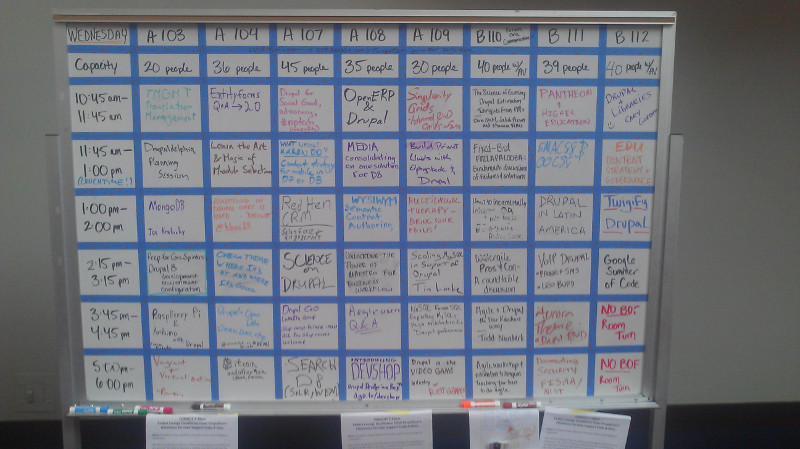 """A whiteboard, showing a grid of different sessions at various times, including such sessions as """"Pantheon and HigherEd"""" and """"Higher Ed Content Strategies"""""""