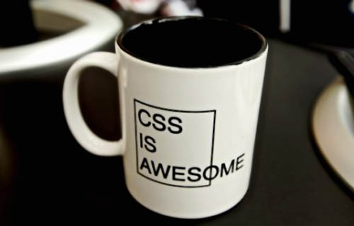 "Coffee mug, with the text ""CSS is Awesome"" overflowing a containing box"
